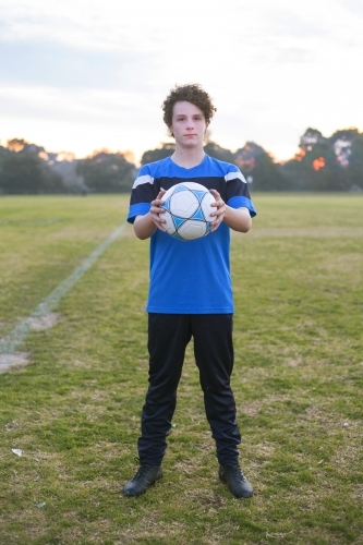 Teenage soccer player on a soccer pitch with ball.