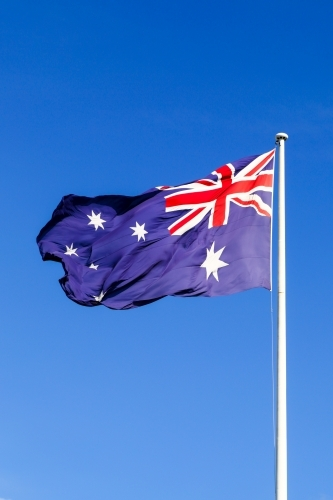 The Australian Flag waving proudly under a clear blue sky