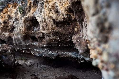 The entrance of a small, dark sandstone cave covered in a variety of tiny naturally embedded pebbles