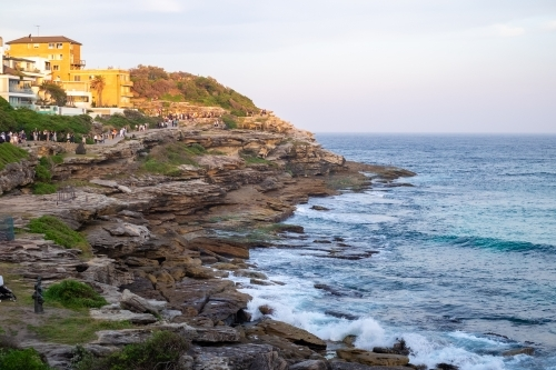 the last rays of the sun, shining on the houses on the cliffs edge of Tamarama