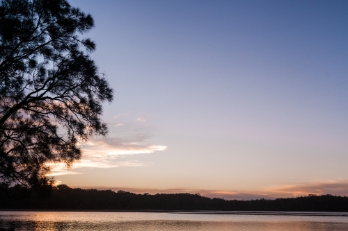 The sun sets behind the silhouette of a tree on the left overlooking a large, smooth lake.