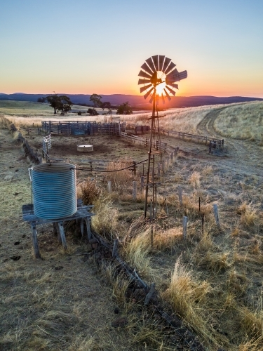 The sun setting behind a still windmill and empty tank on a dry farmland