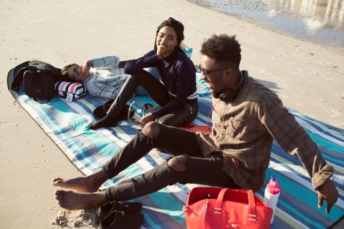Three friends on a picnic blanket relaxing at the beach