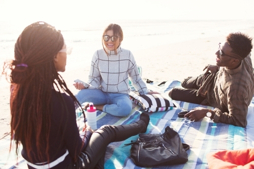 Three friends sitting on a picnic blanket relaxing at the beach