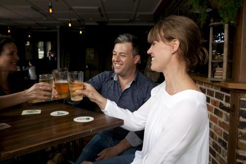 Three friends toasting a drink at local craft beer pub