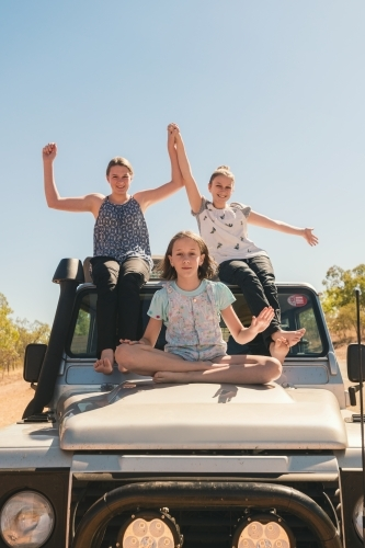 Three girls sitting on the hood of a four wheel drive in outback australia