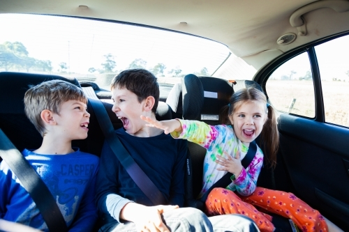 Three happy siblings in the back of a car