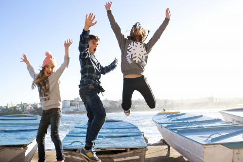 Three kids excitedly jumping in the air off a boat