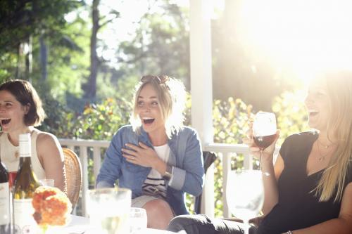 Three laughing women sitting on verandah having drinks