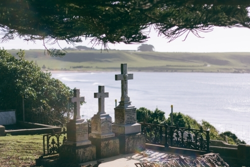 Three old headstones in a graveyard with the ocean in the background