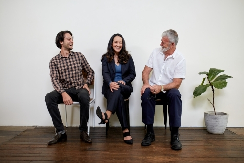 Three professional business people sitting in a row in a studio