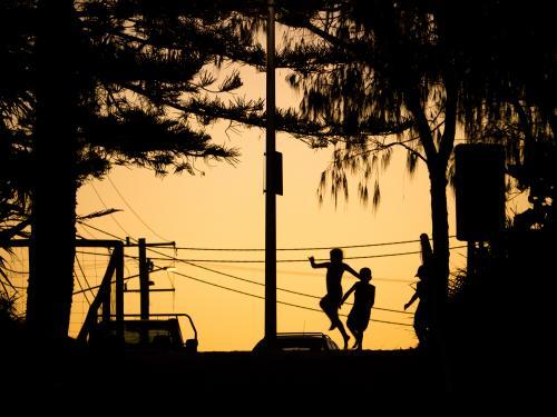 Three silhouetted kids playing in the glow of dusk with power lines