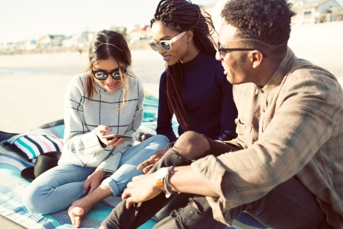 Three teenage friends sitting looking at a phone on a picnic rug