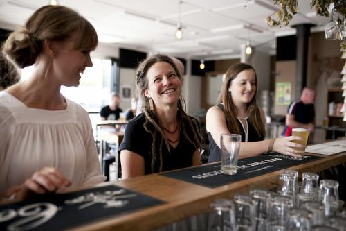 Three women having a drink at the bar of local craft beer bar