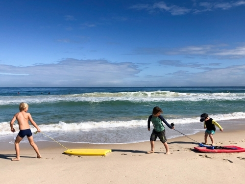 Three young boys dragging boogie boards along the shoreline of beach