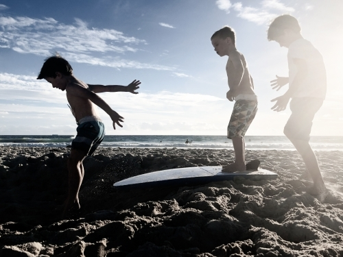 Three young boys playing on beach at sunset with surfboard