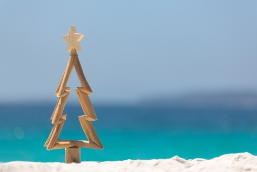 Timber Christmas tree with star sits in pristine white sand with idyllic beach background