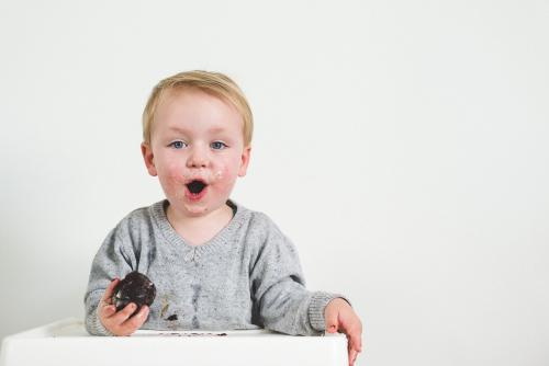 Toddler boy eating chocolate cake in high chair