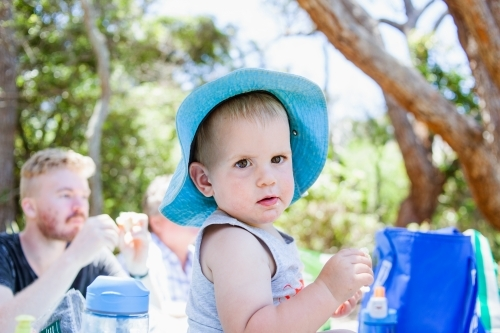 Toddler boy with a blue brim hat, sits on table enjoying picnic with family.