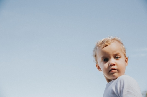 Toddler girl looking straight at the camera framed by blue sky
