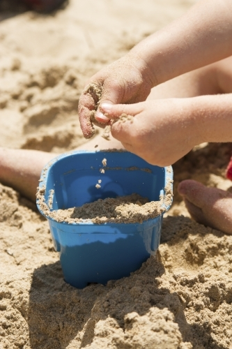 Toddler hands playing with sand at the beach