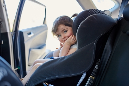 Toddler in child car seat looking at camera