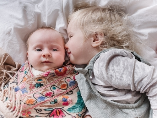 toddler kisses her baby sister.