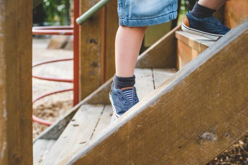 Toddler legs climbing stairs in a playground