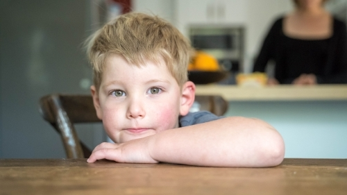 Toddler looking at camera leaning on table