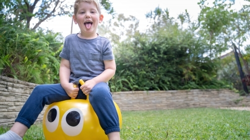 Toddler on jumping ball in backyard