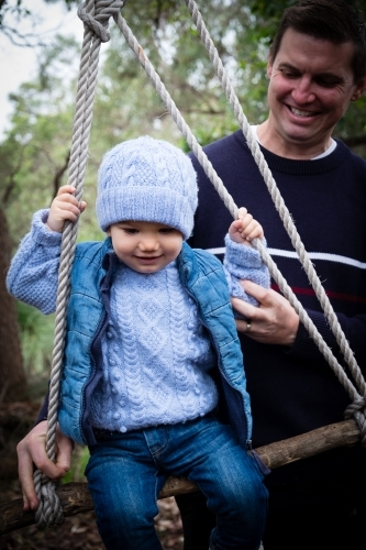 Toddler on rustic swing with father in bush setting