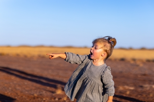 toddler outdoors excitedly pointing into distance