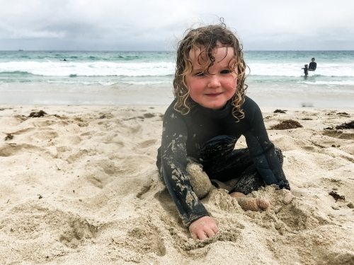 Toddler sitting on beach in wetsuit playing in sand looking at camera smiling