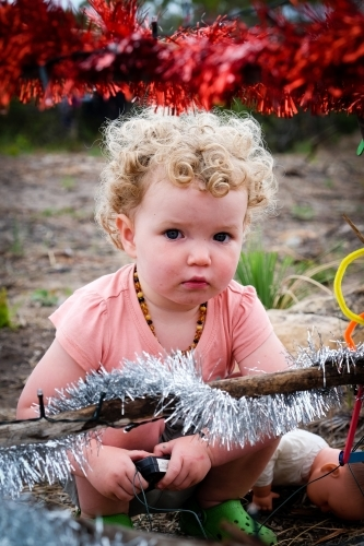 Toddler squatting down behind Bush Christmas tree decorated in tinsel