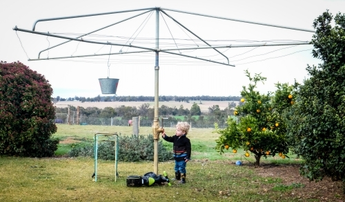 Toddler standing at hills hoist in country setting