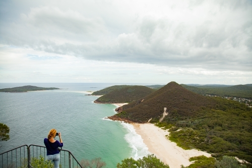 Woman looking out from Tomaree Head Summit walk taking photos of ocean and islands