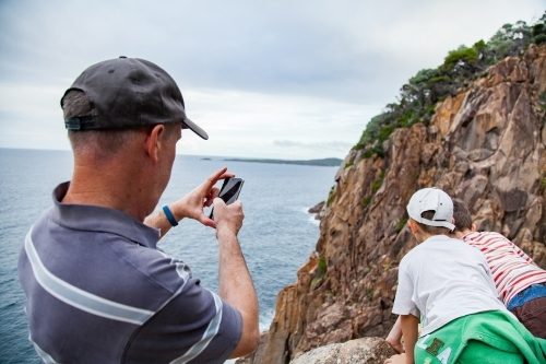 Man taking photos of his boys looking down cliff to the sea