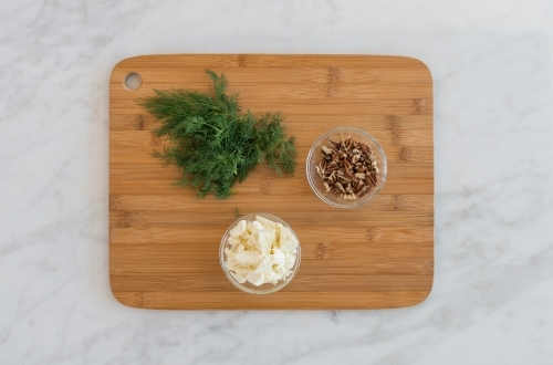 Top down of dill and walnut ingredients on chopping board