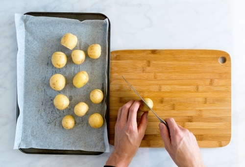 Top down of hands carefully slicing potatoes on bamboo chopping board
