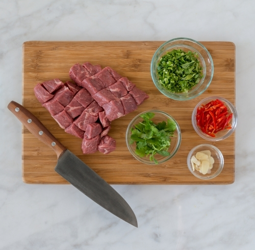 Top down of meat and vegetable ingredients on chopping board