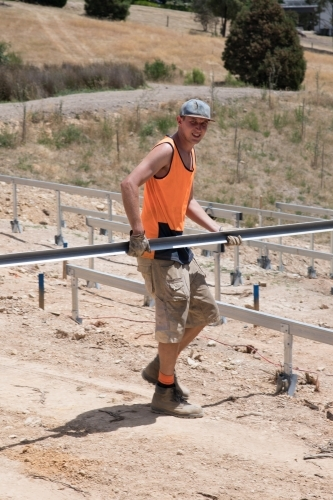 Tradie carrying metal frame on construction site