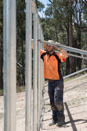Tradie fixing metal house frame on construction site