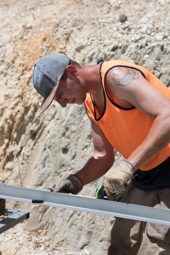 Tradie measuring metal frame on construction site