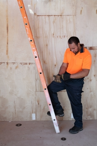tradie putting on gloves before using work ladder