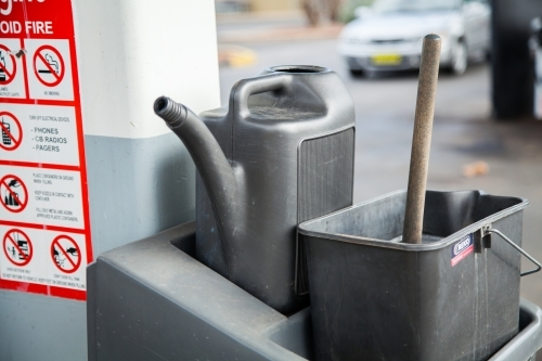 Water can and bucket at petrol station for washing car windscreen