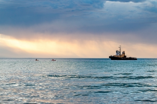 tug boat moored in bay with stormy clouds at sunset