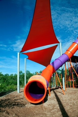 Tunnel slide with red shade sail at playground