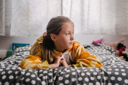 Tween girl in a giraffe onesie lying on her bed, looking away