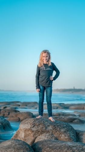 Tween girl standing on rock at the beach