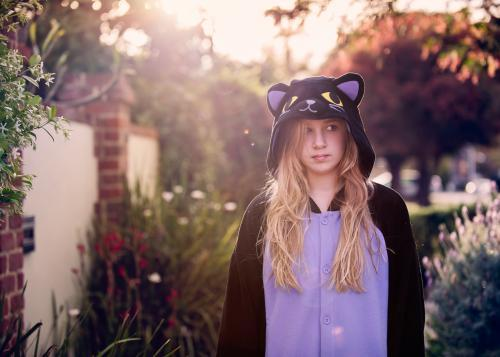 Tween girl with blond hair wearing an animal onesie